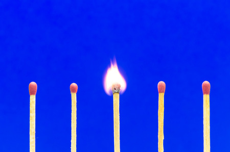 friction: burned match setting on blue background for ideas and inspiration Stock Photo