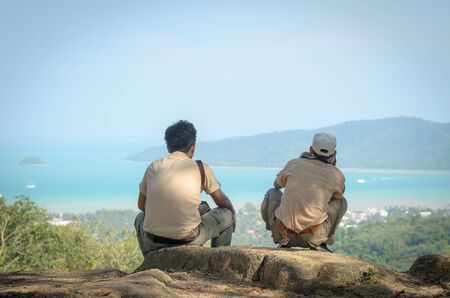 Two men are sitting on hill photo