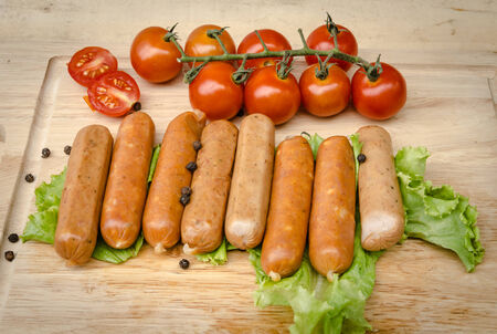A set of sausages and tomato on a kitchen board