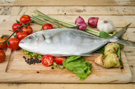 A fish and vegetables are setting on kitchen board