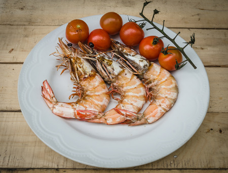 The shrimps are setting on dish with tomato photo