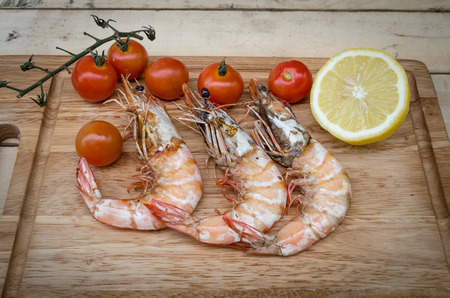 The shrimps are setting on kitchen board with tomato photo