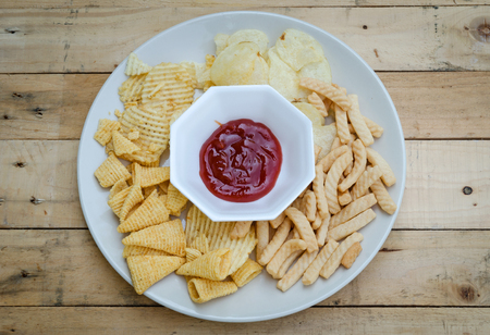 A dish of mix snacks are on wood background.
