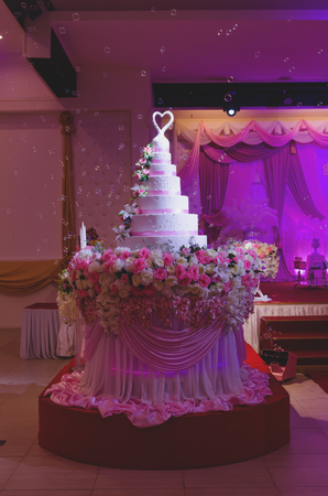 wedding ceremony cake decoration with rose flower at hall Stock Photo