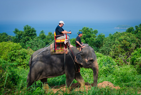 The tourist riding on an elephant behind  the sea background on November 05, 2017 at phuket, south of Thailand Editorial