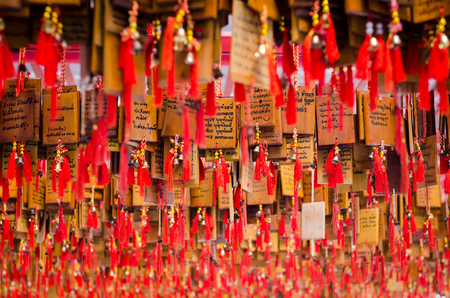 a lot of chinese pray tag are hanging in a chinese temple at Suphanburi province, Thailand