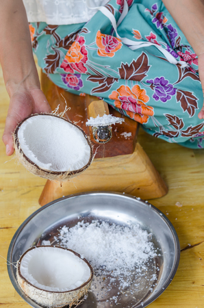 a thai local lady is scraping coconut for making coconut milk.