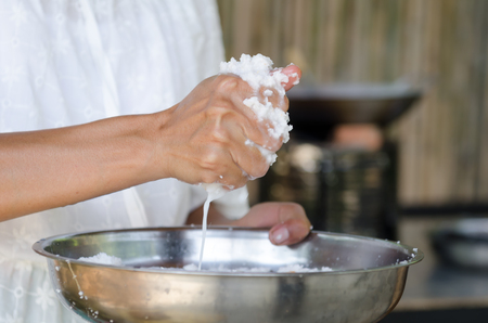 asian woman is making coconut milk for cooking