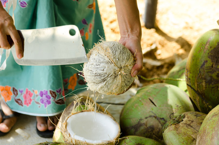 a thai lady is cracking a coconut for making coconut milk.