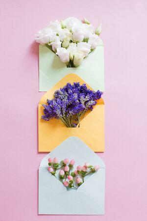 与花的蓝色,黄色和绿色信封里面在桃红色背景
