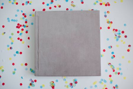 Beige velours book or album for photos without text. Book on the background of colorful confetti