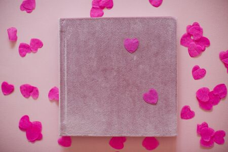 Pink velours book or album for photos without text. Book on the background of heart shaped confetti