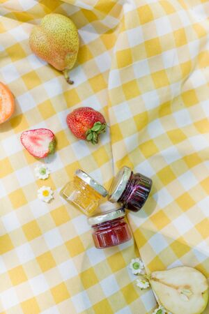 Picnic at the park. Fresh fruits and small jars with tasty jam