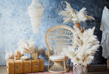 Rattan peacock chair in loft room with boho decorations