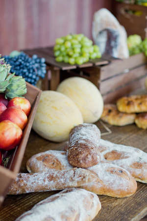 Local food market with vegetables and fruits. Ripe melons, peaches, artichokes and fresh bread on a wooden background