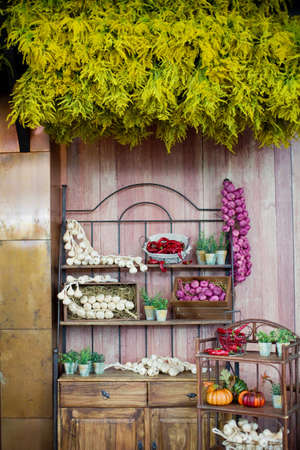 Local food market with vegetables and fruits. Red onions, garlic cloves, chili peppers, pumpkins and herbs in pots