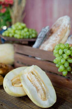 Ripe melon, green grape and fresh bread at farm market