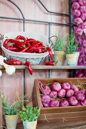 Local food market with vegetables and fruits. Red onions and red chili peppers in baskets