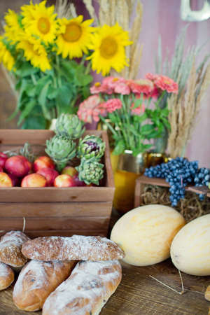 Local food market with vegetables and fruits. Ripe melons, peaches, grape, artichokes and fresh bread on a wooden background Banque d'images