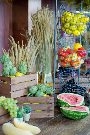 Local food market with vegetables and fruits. Ripe watermelon, artichokes, melon, lemons and peppers in a baskets and wooden boxes Banque d'images