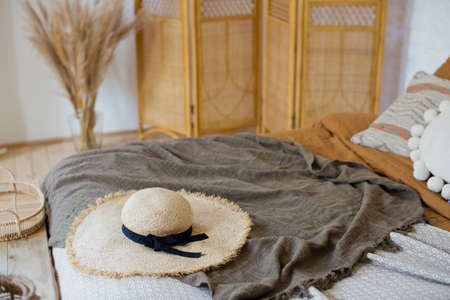 Straw hat on the bed bohemian bedroom. Boho bedroom with bed, pillows and blankets
