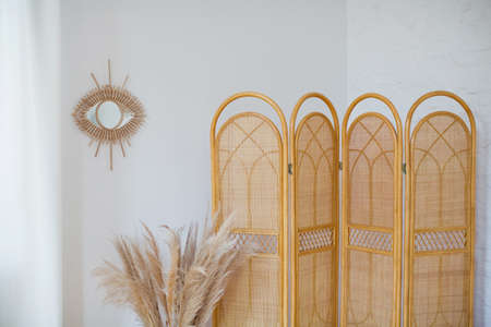Rattan folding screen divider, bouquet of pampas grass and eye mirror on a background of white wall. Bohemian interior details