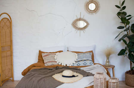 Bohemian bedroom with natural materials decorations. Bed with different pillows and blankets, mirrors on a wall Banque d'images