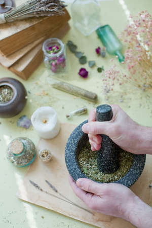 Alternative medicine concept. Man holds black stone mortar and pestle with dry herbs on a yellow background. Dry herbs, bottles, candles and old parchment. Herbal medicine