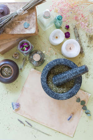 Alternative medicine concept. Black stone mortar and pestle with dry herbs on a yellow background. Dry herbs, bottles, candles and old parchment. Herbal medicine Zdjęcie Seryjne