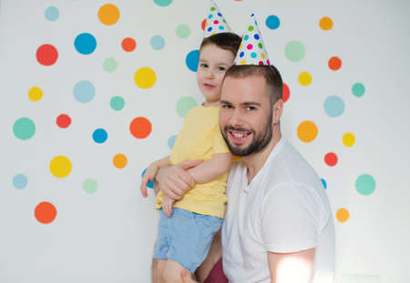 Toddler caucasian boy with his father in the birthday hats on a background of wall with colorful circles