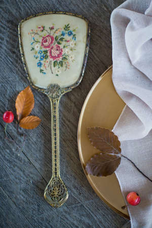 Vintage golden hand mirror and golden tay with red apples on a wooden background