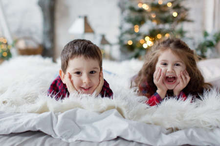 Toddler boy and girl in red shirts lying on the bed near Christmas tree. Cute christmas kids