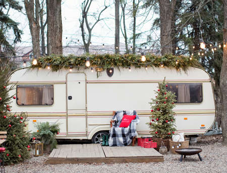 Vintage old travel trailer with Christmas decorations, Christmas tree, chair and Christmas lights. Cozy home, camping before Christmas holidays.