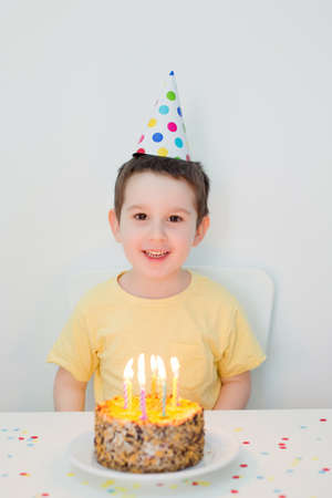 Toddler caucasian boy in colorful birthday hat sitting near birthday cake with blowing candles on a white background