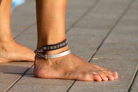 Bare feet on a swimming pool with anklets and bracelets