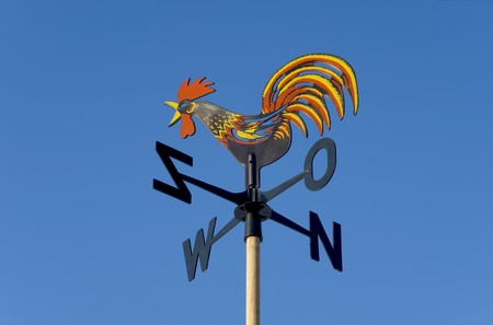 Weather vane against the blue sky Imagens
