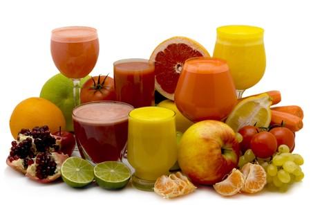 batidos de frutas: Vasos de jugo de frutas con frutas sobre un fondo blanco Foto de archivo