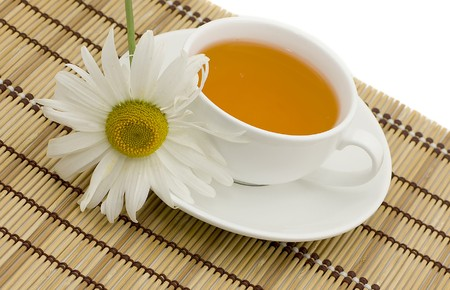 Bright tea in a white cup on a white background photo