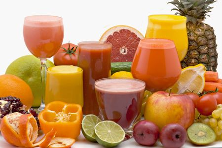 Glasses of fresh juice from different fruit on a white background