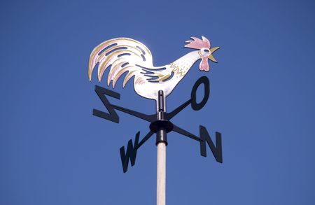 Weather vane - cockerel which reflected sun against bright-dark blue sky photo