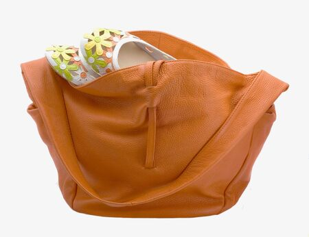 Leather orange bag and shoes-flowers isolated on a white background photo