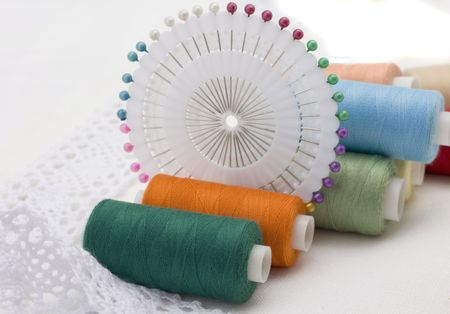 Multi-coloured threads for sewing, needles on  white canvas photo