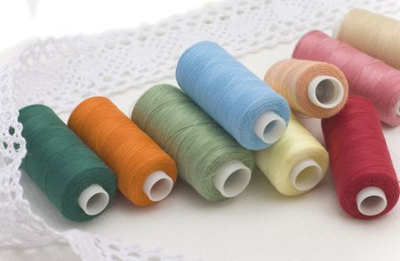 Multi-coloured threads for sewing on a white canvas photo