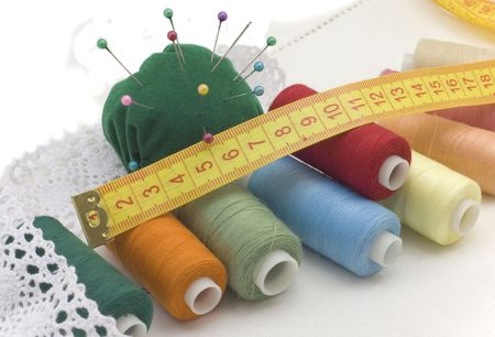 Multi-coloured threads for sewing, needles, a measuring tape on a white canvas photo