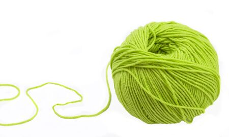 Threads for knitting on spokes of green colour on a white background photo
