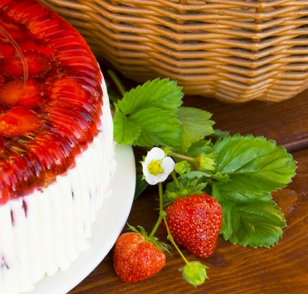 bri: pie, branch strawberry, leaves on wooden table, basket Stock Photo