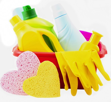 Banks, bottles with washing-up liquids, gloves lie in basin isolated photo