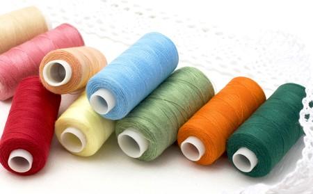 Multi-coloured threads on a white canvas photo