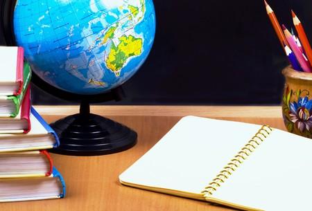 board, globe, books,  pencils, opened empty notebook lie on school desk