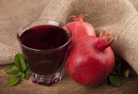 pomergranate: ripe pomergranate and glass of juice on wooden table